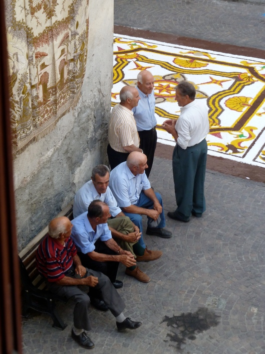 Men on benches in Verbicaro, Italy