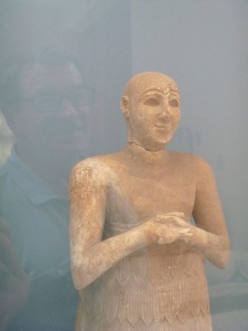 Here is the reflection of my husband trying to look as happy as this ancient figurine.
